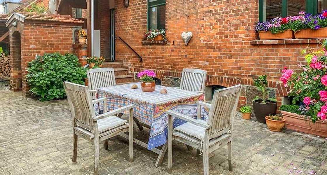 Tisch mit vier Holzstühlen vor einem alten Backsteingebäude (Kuadrathof in Kunow in der Prignitz)